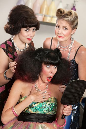 Sympathetic friends and upset woman in beauty salon