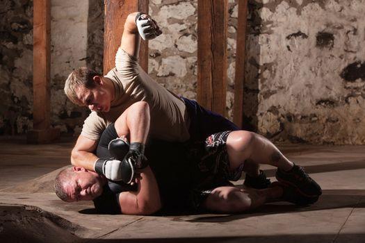 Martial Artist Punching Man on Ground