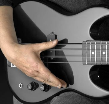 detail of a black bass guitar and hand in dark back
