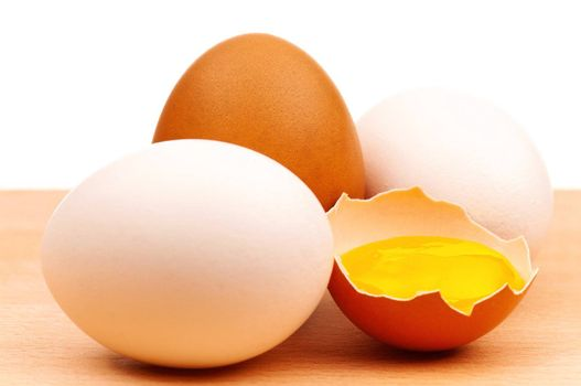 Fresh chicken eggs on wooden board over white background