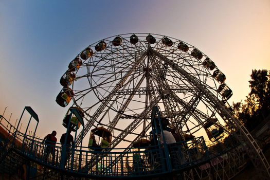 people enjoy the big wheel in the amusement park in Delhi in front of the red fort