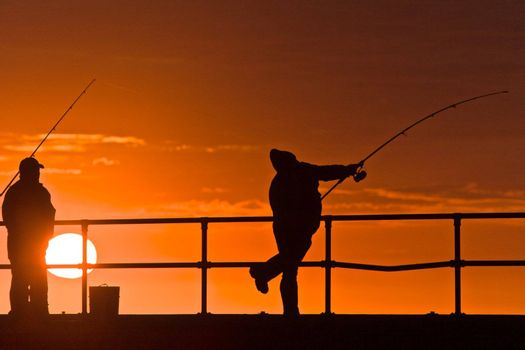 Men fishing, silhouettes with sunset