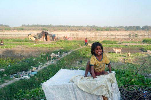 Delhi, India - March 02, 2012: A portrait of a cute poor girl from India.  32.7% of the total Indian people fall below the international poverty line of US$ 1.25 per day while 68.7% live on less than US$ 2 per day.