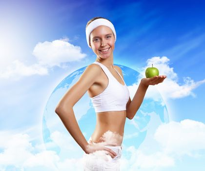 Young pretty girl in sport wear with green apple