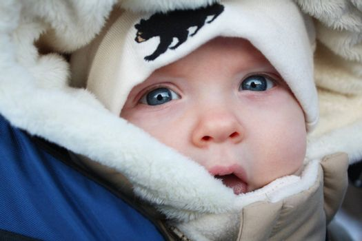 A close up image of a baby in a parka and a tuque