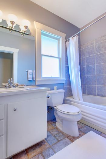 Blue bathroom with white cabinets with stone tiles and blue tiles.