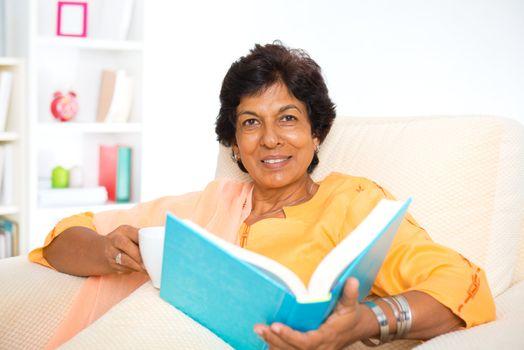 Mature Indian woman reading book