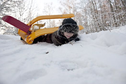 Young boy doing an overturn with a snow sledge