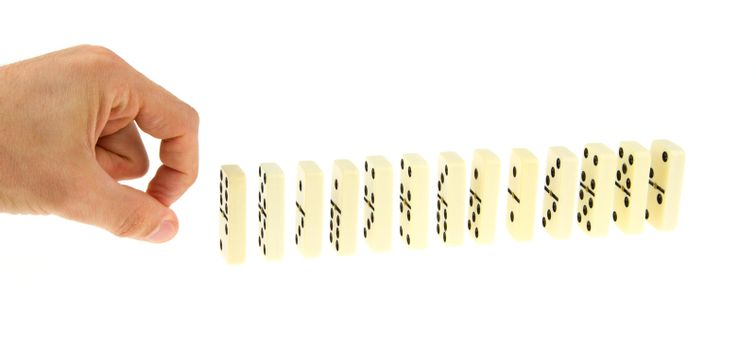 Hand ready to push dominoes in a line to cause chain reaction