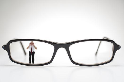 Diminutive elderly man peering through spectacles