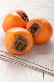Fresh exotic tropic ripe juicy orange fruits  persimmon Diospyros served on textile towel