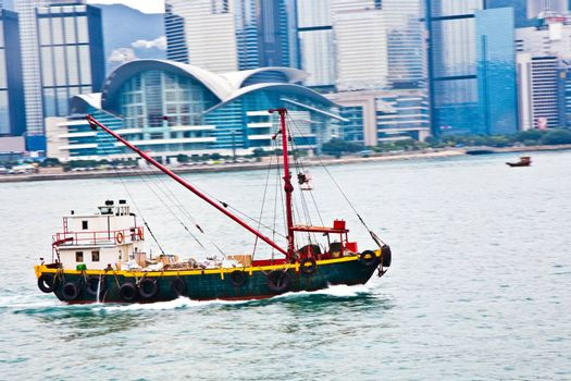 Landscape of Victoria Harbor in Hong Kong with motorboad and people on deck
