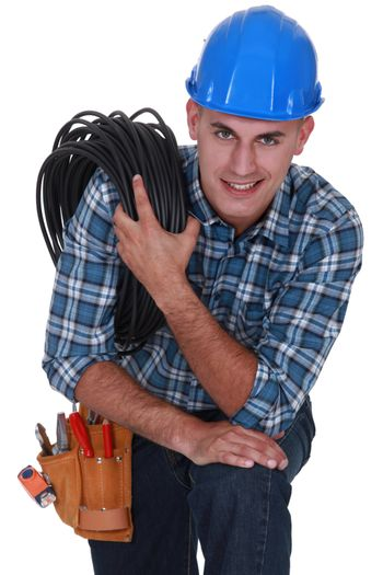 Tradesman carrying a cable coiled around his shoulder