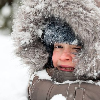 Young boy wearing winter jacket with furry hood playing in snow