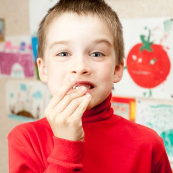 Boy shows lost deciduous teeth against his drawing on the wall