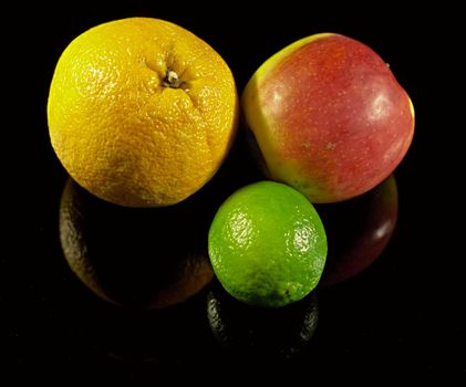 Apple,lemon and orange on black desk with shadows