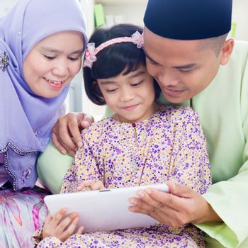 Southeast Asian family surfing internet at home. Muslim family living lifestyle
