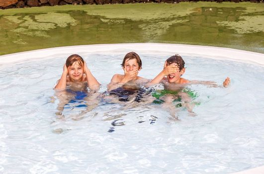 three friends in the pool imitating the three wise monkeys