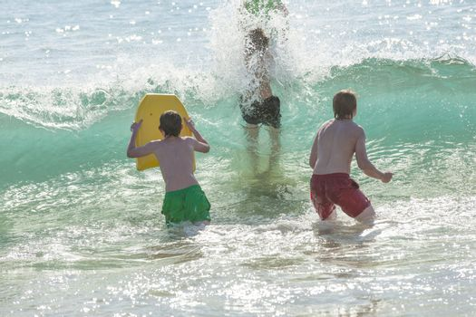boy has fun surfing in the waves