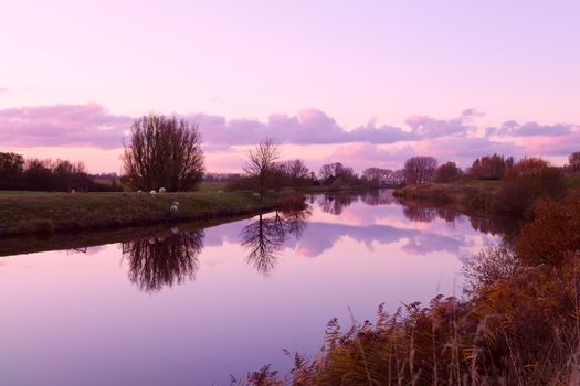 sunset over canal in farmland