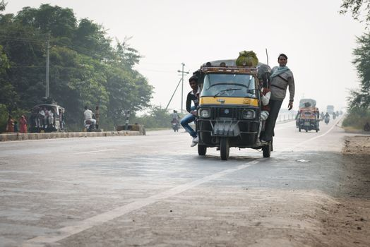 Overloaded and tuk-tuks motorcycles on covered by haze route, Ce