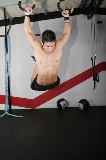 Ring dip crossfit exercise over a dark background.