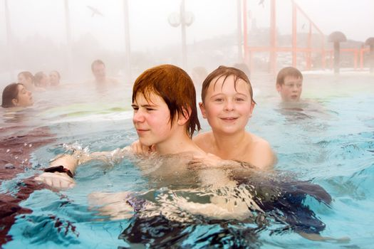 brothers are swimming in the thermal pool in winter