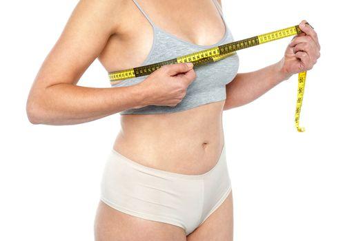 Lingerie clad measuring her breast