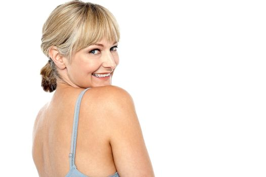 Flirtatious woman turning back and passing a smile