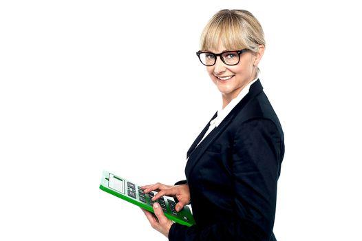 Bespectacled entrepreneur using a calculator