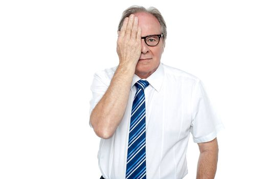 Manager with hand on right eye looking at you