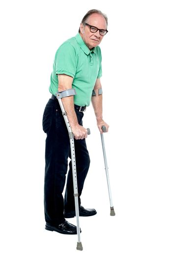 Physically disabled old man with crutches