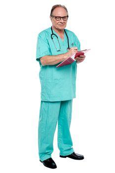 Male doctor in duty hours writing prescription