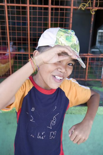 Smiling, healthy, happy, young Filipino boy wearing a hat smiles for his portrait.