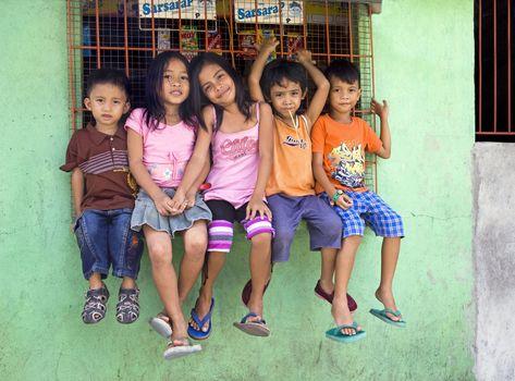 April 2012 - Cadiz City, Negros Oriental, Philippine Islands - Five beautiful young children, boys and girls, sitting on a window ledge in Cadiz City.