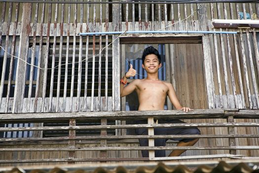April 2012 - Bogo City, Panay, Philippine Islands - A smiling teenage Filipino boy giving thumbs up sign while standing on the porch of his traditional wooden style home in bogo City, Panay, Philippine Islands.