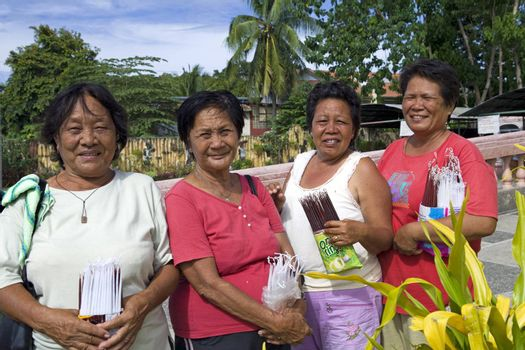 April 2012 - Bogo City, Panay, Philippine Islands - Four senior age Filipino christian women selling devotional candles outside the local Catholic church in Bogo City, Panay, Philippine Islands.