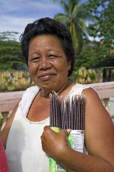 May 2012 - Bogo City, Cebu Island, Philippines - Middle-aged Filipino woman sells votive candles near the Catholic cathedral in Bogo City, Cebu, Philippines.