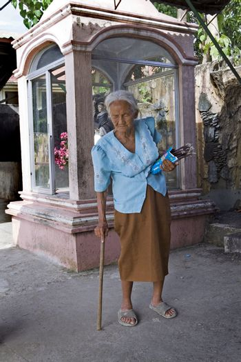 May 2012 - Bogo City, Cebu Island, Philippines - Elderly, blind Filipino woman walking with a cane selling votive candles near a Catholic christian shrine. Senior citizens are held in high respect in the Philippine culture no matter how old they are.