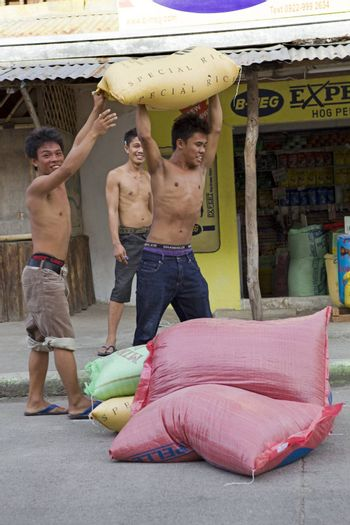 May 2010 - Bogo City, Cebu, Philippine Islands - Three teenage boys carrying 50 kilo sacks of white rice to a storage warehouse. Rice is the most important grain crop in the Philippine Islands.