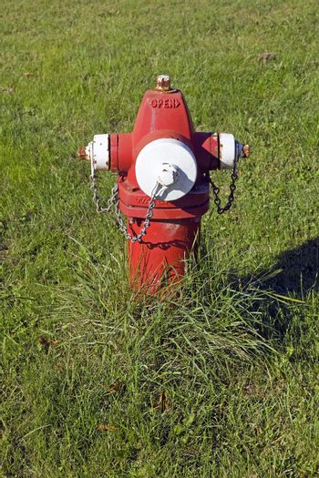 Old fashioned red fire hydrant sitting in a field of grass.