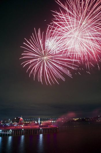 Montreal, Quebec, Canada - Night fireworks display. Jacques Cartier bridge visible in the distance.