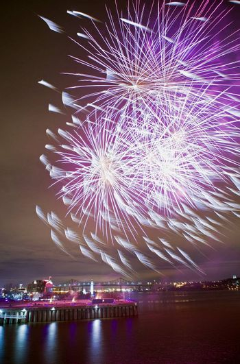 Montreal, Quebec, Canada - Night fireworks display strong wind feathering some of the bursts like horsetails. Jacques Cartier bridge visible in the distance.