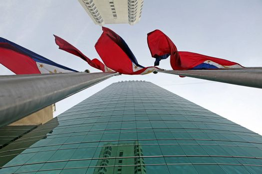 Manila City; Luzon; Philippine Islands - Four red, white and blue Philippine national flags waving in the wind in downtown Manila City on tall flagpoles. Modern skyscrapers border the flags.