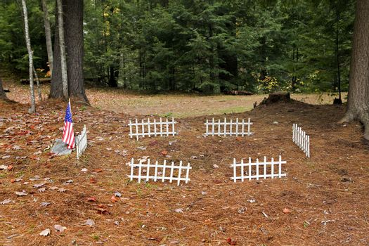 American flag and white fence surround a war veteran grave located in a wooded cemetary area with ground covered in pine needles.