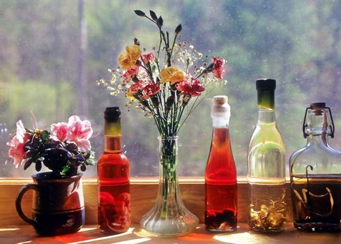 Four herb and fruit vinegar bottles on a windowsill next to two containers of flowers.