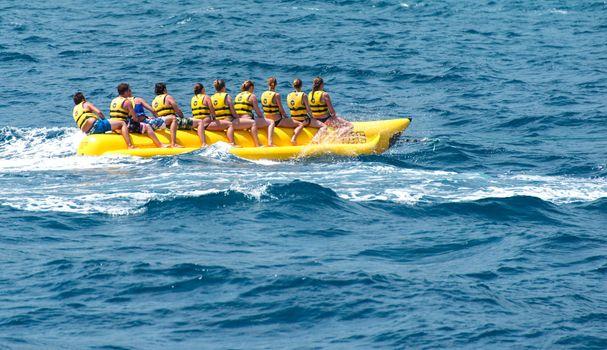 People riding banana boat at sea