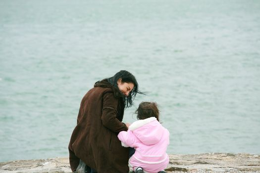 Back view of mother and daughter in beautiful spring sea