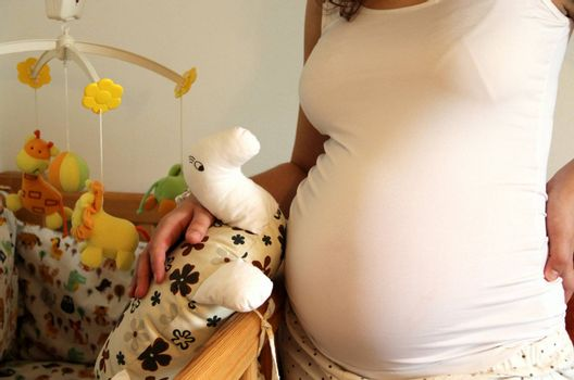 Pregnant woman tummy, baby bed and toys