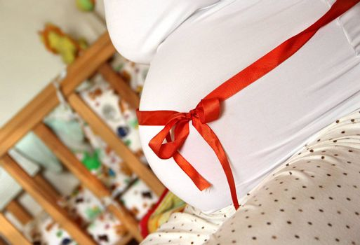 Pregnant woman tummy decorated with red ribbon and bow
